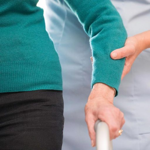 A older woman wearing a green jumper is helped with her walking apparatus by a care worker dressed in a blue uniform