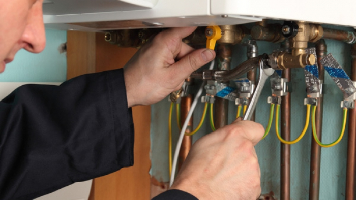 Plumber fixing a boiler on home visit