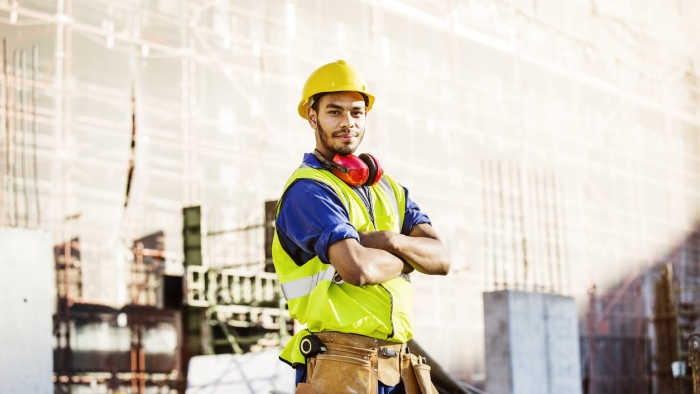 Portrait of confident construction worker in protective workwear standing arms crossed at site