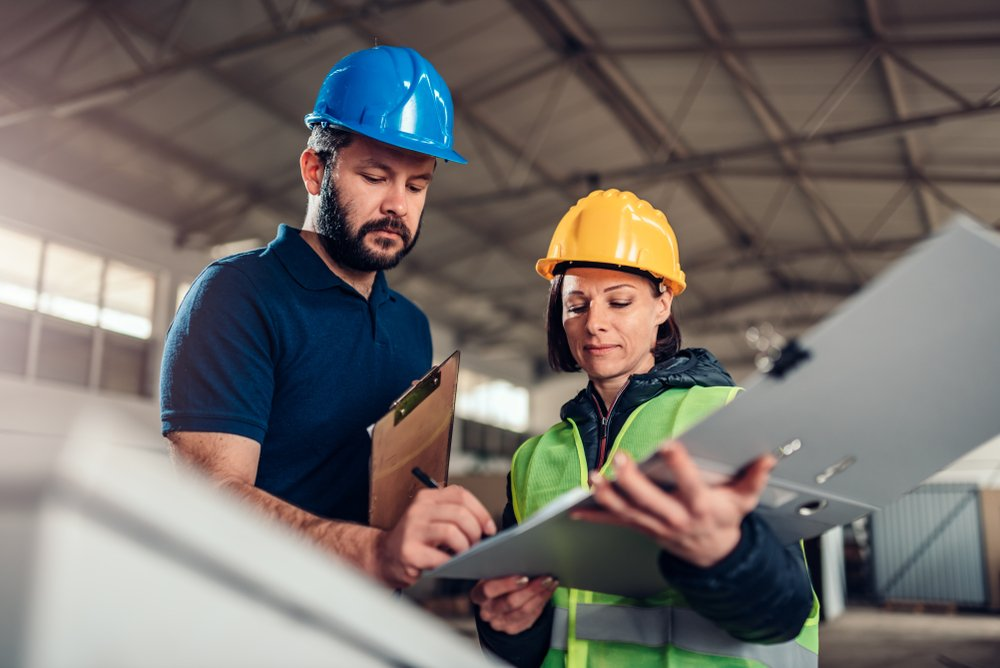 Male and female construction worker going over plans