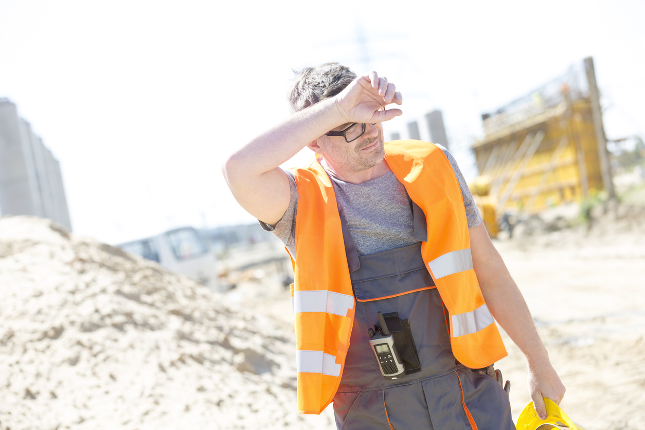 Tired construction worker wiping forehead at site in hot weather