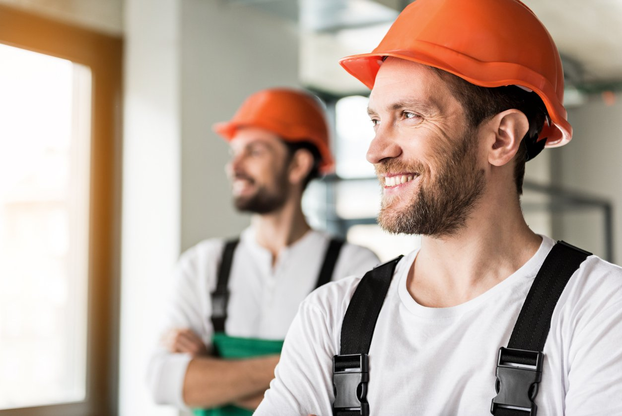 Hilarious smiling construction workers in room