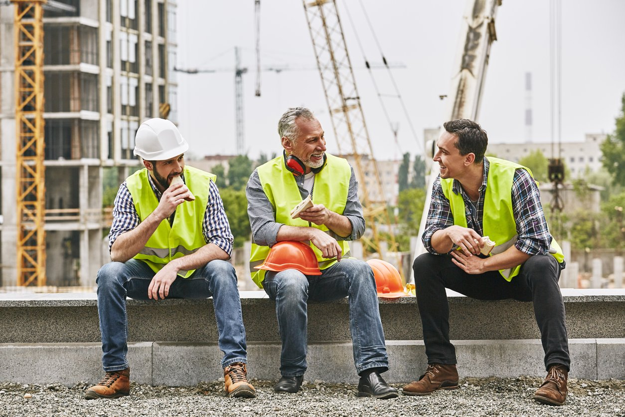 Group of contractors laughing on a wall during break
