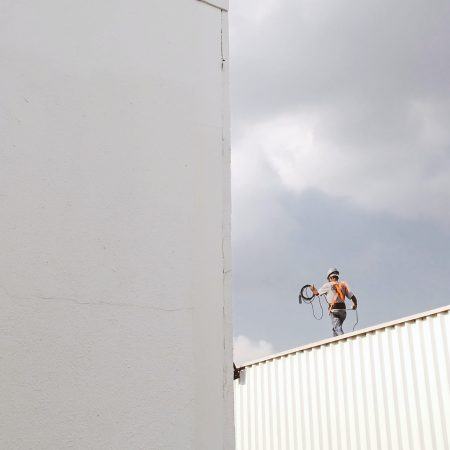Worker walking on roof top carrying wire